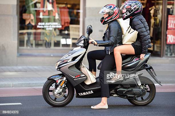 Two women riding vespa in central stockholm