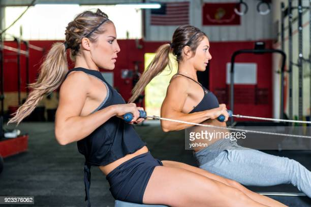 Two women rowing with power at gym