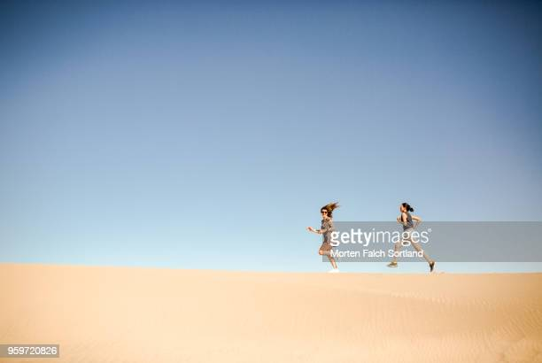 Two Women Run along a Sand Dune in Death Valley, California Summertime