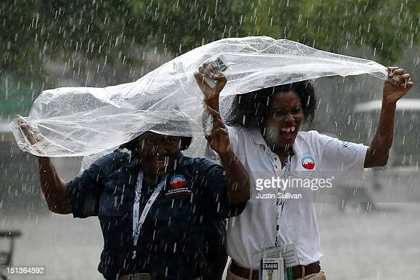 Two women run for cover from the pouring rain during the final day of the Democratic National Convention outside the Time Warner Cable Arena on...