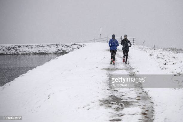 Two women run in snowy conditions alongside Brun Clough Reservoir as snow falls above the village of Delph, near Manchester in northern England on...