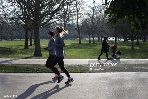 Two women run in Victoria Park in East London during lockdown 3 on the 13th of February 2021, London, United Kingdom. During the national coronavirus...