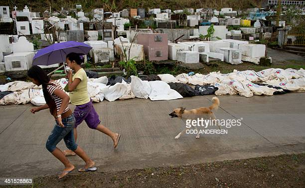 Two women run past a row of super typhoon Haiyan victim bodybags awaiting burial in a massgrave at a cemetery in Tacloban on November 23 2013 The...