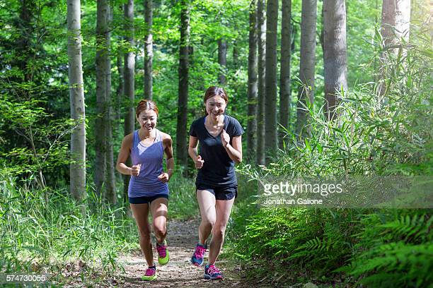 Two women running in a forest