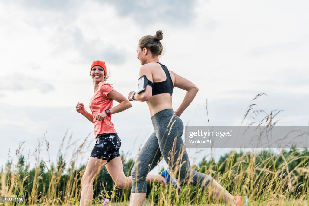 Two women running in the countryside : Stock-Foto