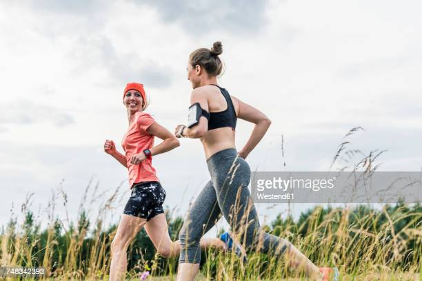two women running in the countryside - freizeitaktivität stock-fotos und bilder