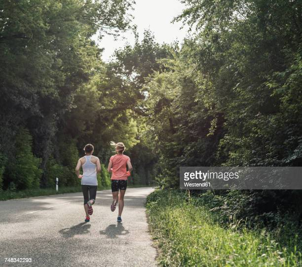 Two women running on country road