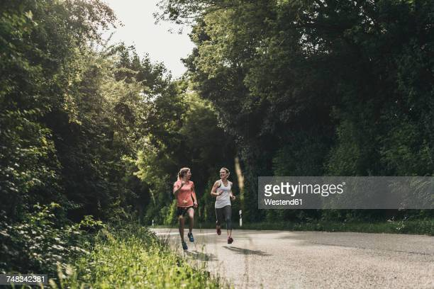two women running on country road - endurance stock photos and pictures