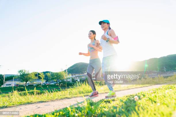Two women running on river side