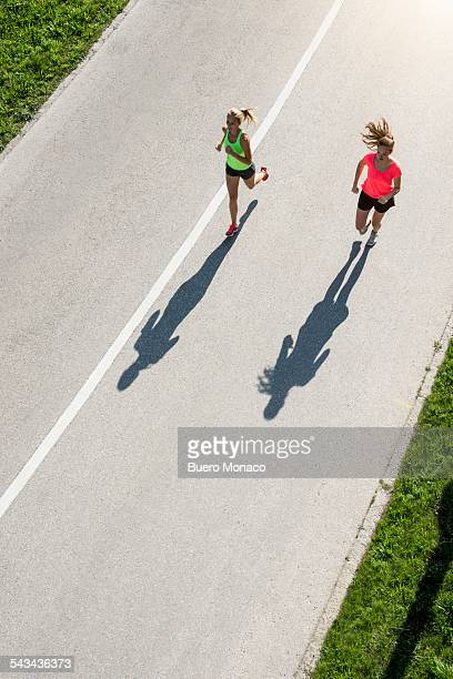 two women running on street, high angle view