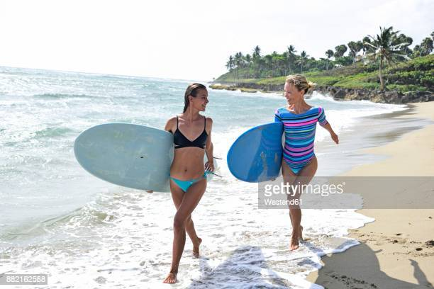 Two women running on the beach with surfboards