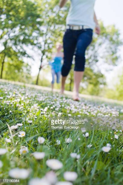 Two women running through a field filled with daisies