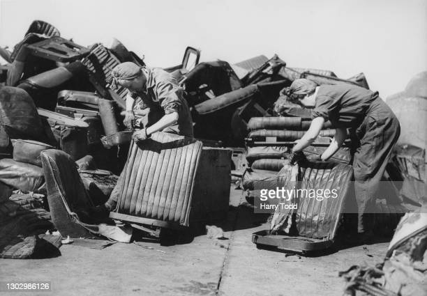 Two women salvage workers strip down the leather upholstery from scrapped motor vehicle seats at the Crystal Palace scrap yard as part of the...