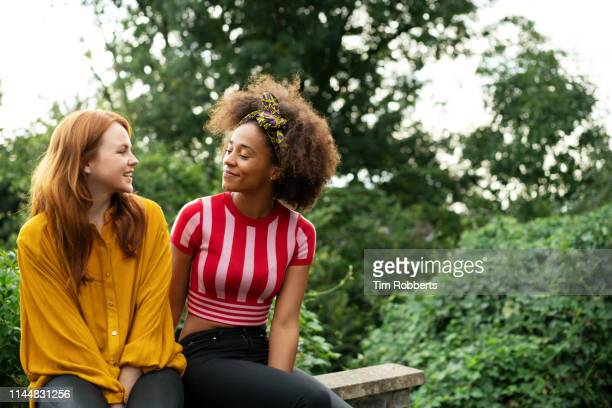 two women sat on wall - friendship stock pictures, royalty-free photos & images