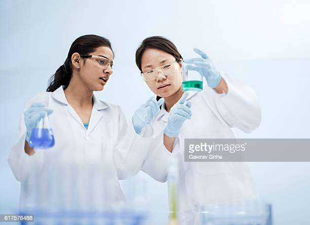 Two women scientists working in a laboratory with chemicals.