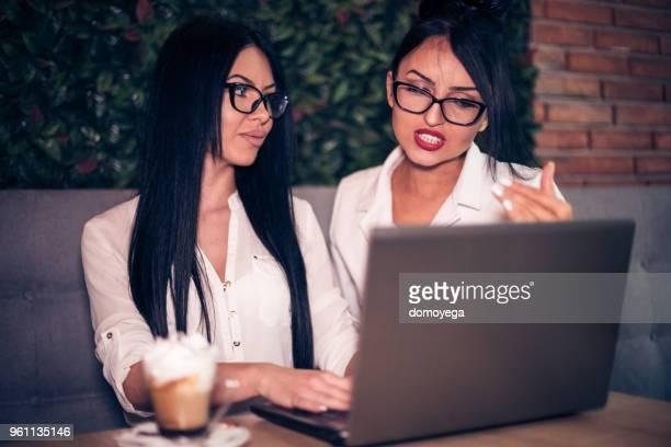 2 人の女性の検索とコーヒー ・ バーでノート パソコンを使用
