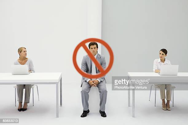 Two women seated in front of laptop computers, warning sign over man frowning between them