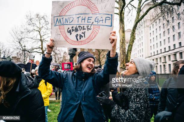 Two women seen laughing while holding a placard during the march Scores of women across the United Kingdom took to the streets on Sunday to protest...