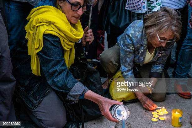 Two women seen lighting candles in the center of the Catalunya Square in memory of the 1050 days in prison of the Catalan political prisoners A...