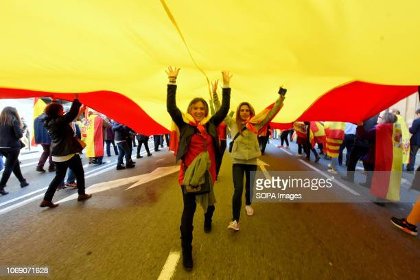 Two women seen under a great flag of Spain during the event Two thousand people celebrated the 40th Anniversary of the Spanish Constitution in...