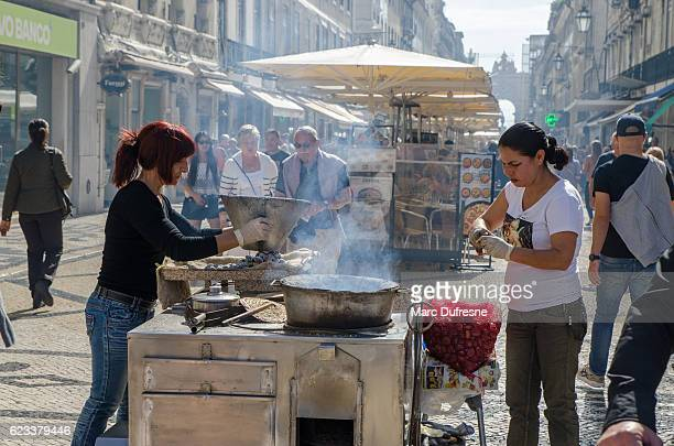 two women selling roasted chestnuts on rua augusta - rua stock pictures, royalty-free photos & images