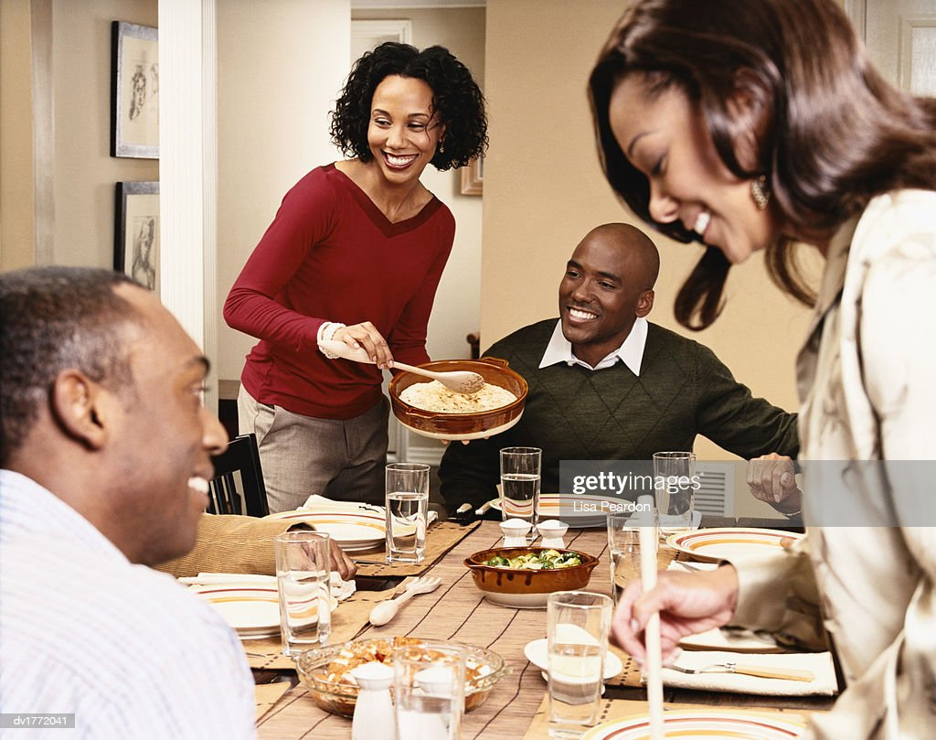 Two Women Serving Food To Two Men At A Dining Table Stock Photo ... 845de6432
