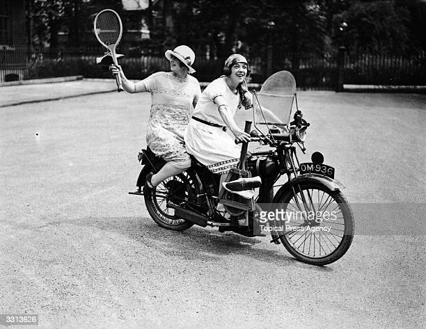 Two women set off on a BSA motorbike to play tennis after work.