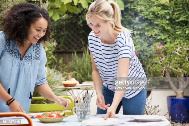 Two women setting table for garden party.
