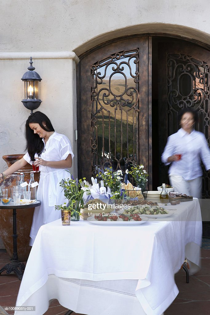 Two women setting table of appetizers, wrought iron door in background : Stockfoto