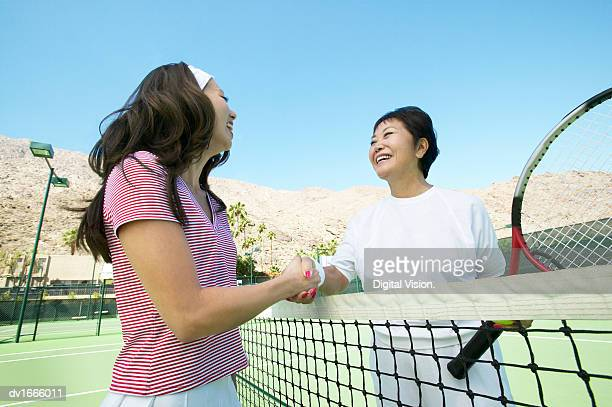Two Women Shaking Hands over a Tennis Net