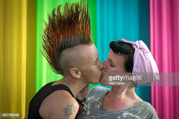 Two women share a kiss below the Ribbon Tower in The Park at Worthy Farm in Pilton on the eve of the first day of the 2014 Glastonbury Festival on...