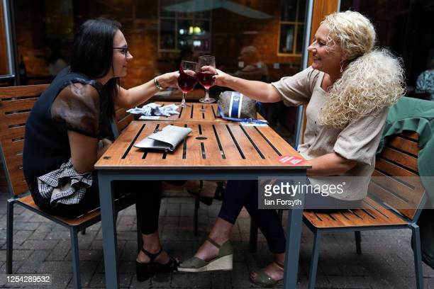 Two women share a toast as they have a glass of wine on the first day of pubs reopening at the Job Bulman pub in Gosforth on July 04 2020 in...