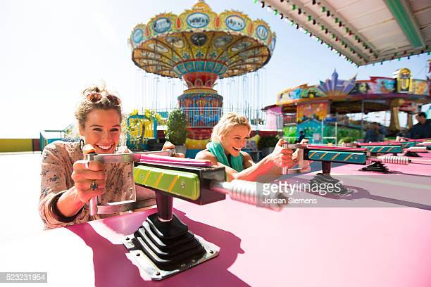 two women shooting squirt guns at carnival - 遊園地 ストックフォトと画像