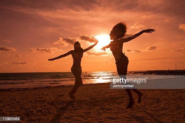 Deux femmes silhoetted s'amusant à e beach