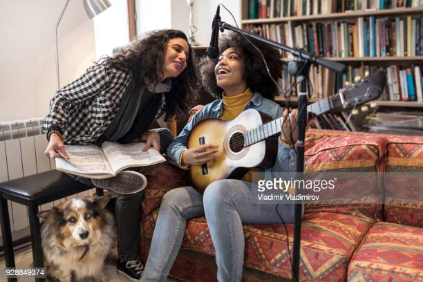two women singing and playing the guitar in studio - songwriter stock pictures, royalty-free photos & images