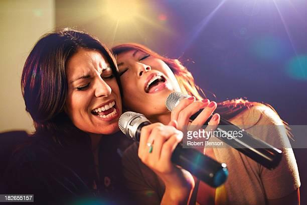Two women singing karaoke.