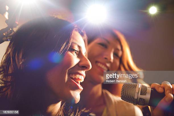 Two women singing karaoke.