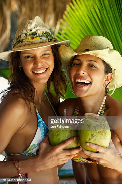 Two women sipping coconut with straw, smiling, portrait