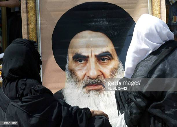 Two women sit in a cart as a man tries to sell them a large poster of Grand Ayatollah Ali Sistani, in the Kazemiya neighborhood of Baghdad 19 May...