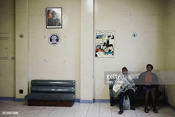 Two women sit in a railway waiting room beneath the ubiquitous portrait of their president Robert Mugabe in Harare Zimbabawe on November 2nd 2016...
