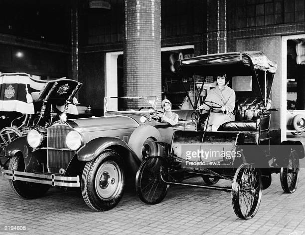 Two women sit in the driver's seats of adjoining cars in an automobile showroom, one an antique and the the other a new Packard Sedan, circa 1920.