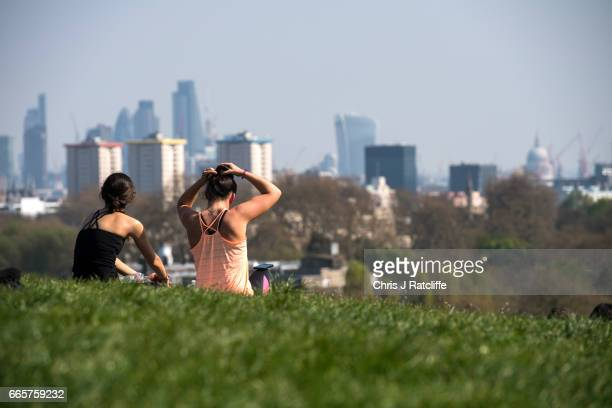 Two women sit in the sun as one ties her hair into a bun whilst overlooking London on Primrose Hill on April 7 2017 in London England Temperatures...