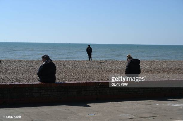 Two women sit on a wall keeping a gap to observe social distancing on the beach front in Brighton southern England on March 24 2020 after Britain...