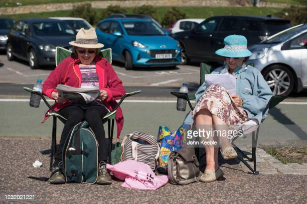Two Women sit on camping chairs and read the newspaper beside at the beach on March 30, 2021 in Southend, United Kingdom. Despite todays temperature...