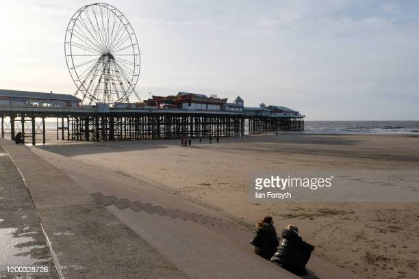 Two women sit on sea defence steps near the Central pier on Blackpool seafront on January 18 2020 in Blackpool England Warmer weather has taken over...