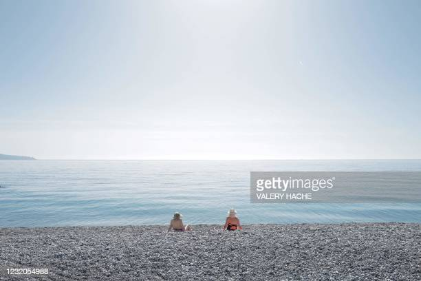 Two women sit on the beach in front of the Mediterranean sea on the French Riviera city of Nice, on April 1, 2021.