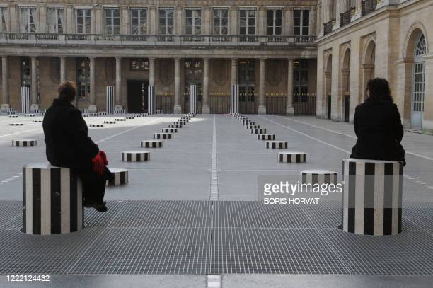 Two women sit on the Daniel Buren columns set up in the inner yard of the Palais Royal in central Paris on March 17 2010 AFP PHOTO BORIS HORVAT