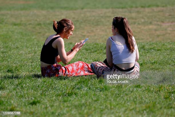 Two women sit on the grass enjoying the holiday sunshine in Alexandra Park in north London on April 10 2020 as warm weather tests the nationwide...