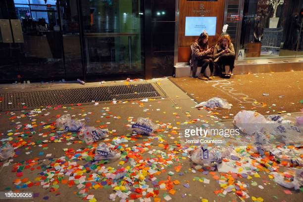 Two women sit outside of a hotel amidst confetti and debree left behind after thousands of revelers gathered in New York's Times Square to celebrate...