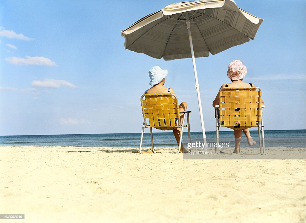 Two Women Sitting a Chairs Under a Parasol on the Beach : Stock Photo